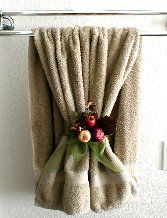 "This bathroom towel decor is simply a sheer green organza ribbon tied in a bow around one layer of the towel with a pomagranate ""Pick"" placed behind the ribbon."