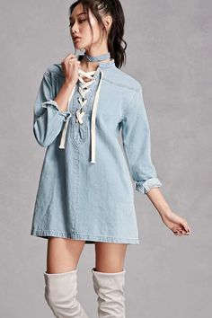 A denim shirt dress featuring a boxy cut, a contrast lace-up front with grommets, a high collar, on-seam pockets, and long sleeves. This is an independent brand and not a Forever 21 branded item.