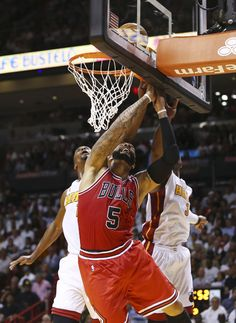 Miami Heat's Chris Bosh (1) and Dwyane Wade (3) defend on a shot by Chicago Bulls' Carlos Boozer (5) during the second half of an NBA basketball game in Miami, Tuesday, Oct. 29, 2013. The Heat won 107-95. (AP Photo/J Pat Carter)
