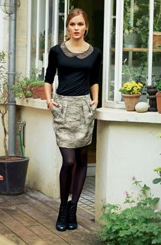 Collant noir, jupe courte, haut à col Claudine, queue de cheval, style vestimentaire classique