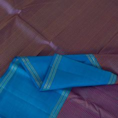 This enigmatic Kanjivaram silk sari is an alluring beauty! The soft purple body is adorned by thread work waves in blue-yellow silk. The dodger blue pallu is brightly embellished with graceful annams, gentle elephants, majestic yazhis, diamond motifs and floral bhuttas in silver coloured zari. A thick band of dodger blue borders the sari on either side. A contrasting dodger blue blouse carrying the same border completes the attire. Code 180121827.