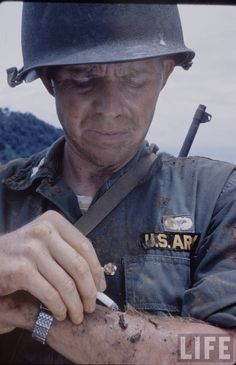 U.S. Army officer in Vietnam using a cigarette to burn leeches off his forearms, photograph by Larry Burrows.