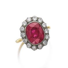 ATTRACTIVE RUBY AND DIAMOND RING Centring on a cushion-shaped ruby, within a frame of circular-cut diamonds