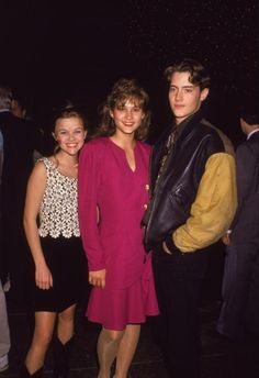 Reese Witherspoon stands and poses with actors Emily Warfield and Jason London at an event circa 1990s