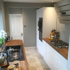 Minimal white kitchen with grey walls, wooden worktop, travertine floor.
