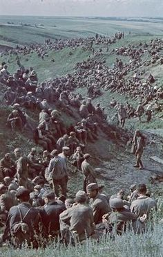 Soviet Red Army prisoners of war over the landscape.. Seemingly indifferent about their situation, as if glad to be taken out of the fighting. There are no guards in sight. Their uniforms suggest summer weather, perhaps mid-, late 1941, when large numbers have surrendered to the attacking Germans (Operation Barbarossa).