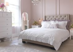 Feminine pink bedroom with crisp white bedding and white chest of drawers.