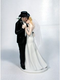 western wedding cake topper groom wears cowboy hat and boots bride wears dress and cowgirl boots