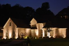 custom landscape lighting illuminating the outside walls of a brick house