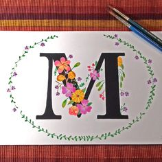 Letra M personalizada com muitas flores alegres e com cores vivas. Para encomendar seu monograma, é só mandar um e-mail para falecom@acasalaranja.com.br