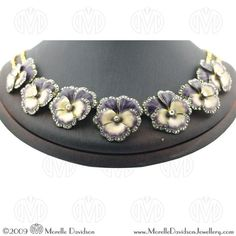 Gold, enamel and diamond graduated pansy necklace. Each violet and white enamel flower head within a diamond set surround, accented by a central rose cut diamond.