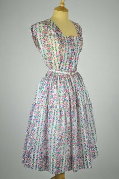 This pretty 1950s vintage dress is by St Michael, and is made of ivory nylon with a lovely floral pattern in blue, pink and green.