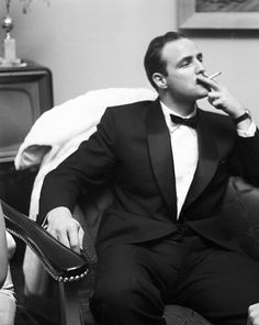 Original Caption: Actor Marlon Brando smokes a cigarette as he attends a party on February 24, 1955 in Los Angeles, California.