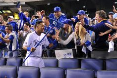 Oct 15, 2014; Kansas City, MO, USA; Kansas City Royals catcher Salvador Perez (13) celebrates with fans in the stands after game four of the 2014 ALCS playoff baseball game against the Baltimore Orioles at Kauffman Stadium. The Royals swept the Orioles to advance to the World Series. (Peter G. Aiken-USA TODAY Sports)