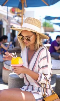 Striped jumpsuit with oversized sunglasses and a wide brim straw hat, and shaved ice!