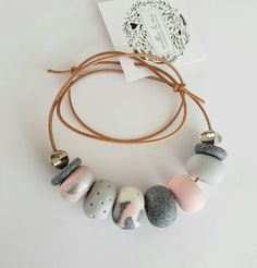 A beautiful simple necklace that has a combination of colours that ooze prettiness. Each clay bead is rolled and formed by hand. The clay beads are strung together on a genuine natural leather cord. This necklace is adjustable in length. This necklace is made to order.
