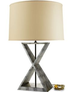 "L4 lamp by Gracie makes a graphic yet elegant statement. Standing 27"" tall, shade included, the lamp features a wood base finished in either antiqued silver- (shown) or gold-leaf tea paper"