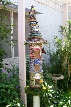 Add some whimsy to your backyard with a storybook-worthy fairy house. This one has three little homes sitting atop one another, each with their own flair from different china patterns. Learn more at Whimsical Mosaics.