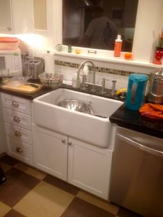 Shaw original fireclay single bowl apron farm sink (weighs 161 lbs) with black granite countertops, white cabinets, checkerboard floor.