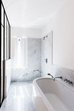 Gorgeous bathroom renovation -- love the open plan, marble, and bright white standing tub. So modern and sleek!