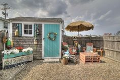 Cottage Patio with Cedar shingle siding, Outdoor umbrella, Nautical themed, Flower planter, Garden shed, Raised beds, Fence