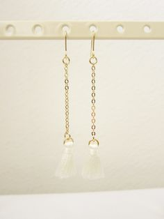 Dangling white tassle earrings ($12.50) The dangling white tassle earrings are the must-have accessories for anyone who wants to add a stylish touch to their outfit. The white tassle can be easily paired with any color. Made in Korea.