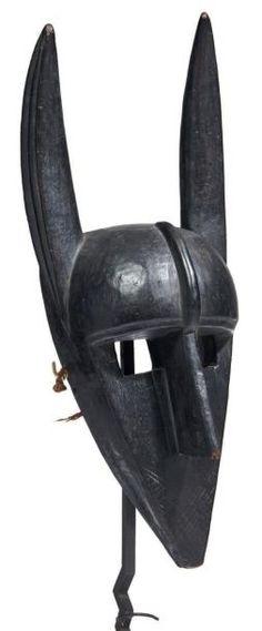 MASQUE en bois animalier représentant la hyène mythologique «Suruku» dispensant ses secrets initiatiques aux hommes. Ce masque associé à la société secrète du «Koré» apparaît comme un exemplaire particulièrement réussi sur le plan de la rigueur de la construction des volumes ainsi que par son ancienneté et sa patine quasi laquée. Bambara. Mali Provenance: objet acquis sur le marché parisien dans les années 80. H_46 cm
