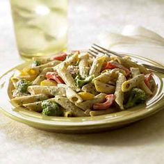 Creamy basil sauce smothers pasta, chicken and vegetables for a healthy hearty family meal in this main dish recipe.