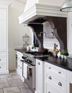 gorgeous white kitchen design with white kitchen cabinets, subway tiles backsplash, pot filler, soapstone counter tops, corbels and stone floors.