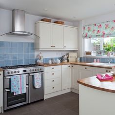 Neutral floral kitchen. The simple units and wooden worktops provide the perfect backdrop for pretty crockery and floral furnishings.