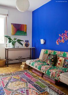 Quarto de hóspedes com parede azul, manta e tapete com estampas étnicas e pendente japonês.