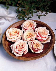 Instead of decorating tables with large arrangements, float a few flowers in shallow bowls or glass cylinders filled halfway with water