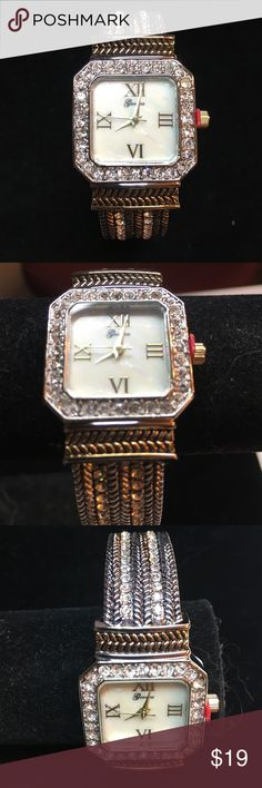 Silver and gold watch. Silver and gold Watch.  Like mother of pearl face. Has the red plastic at stem to save battery.  Crystal stones around the square face. Never been worn.  Hinges open. Accessories Watches