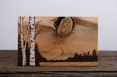 This woodland scene has been burnt into a piece of salvaged cedar and features a unique knot in the wood as the setting sun. I have added white