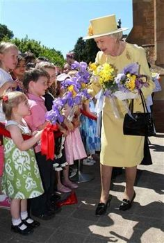 Queen Elizabeth II receives flowers from children after church services at St. John's in Canberra