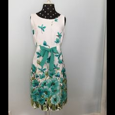"ListingGorgeous Floral Print Dress This Lovely Sleeveless Dress is ""Sprinkled"" with Flowers both front and back with Florals settling heaviest near hemline. Beautiful shades of Aqua, Lt. Blue and Teal are accented in Black on a White background. This dress would be perfect for a Summer Wedding! It is Belted at waist with a wide Teal Grosgrain Ribbon tie. Back zipper; hook/eye closure. Made of 97% cotton/3% spandex. Hand wash/dry flat. NWOT. Never worn - it just is too big. *(Shoes/Slides are…"