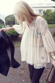 sheer, cream flowy tunic top + loose blonde locks + gold arm party + sleek black leggings