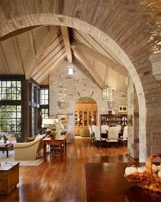 open concept living, stone walls, wide plank wood floors