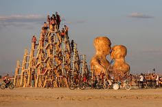 People climb up an art installation as the Burning Man 2014 arts and music festival kicks off in the Black Rock Desert of Nevada
