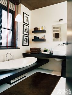 In the bath of a Milan apartment, the rounded forms of Boffi's Adda sink complements the thick custom wenge wood counters and shelves