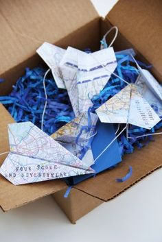 DIY map paper airplane garland with stamped message (optional). Nice party decoration or gift: print or cut a map of the location your going to, fold into a plane and stamp or write your message.