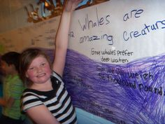Student shows the class project: a life-size whale poster filled with facts.