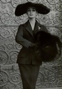 Christian Dior suit with a fox fur muff and wide brimmed hat. 1954