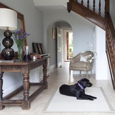 Update a wide, traditional country house hallway with a simple but striking neutral scheme including powder blue walls, limestone flooring and elegant soft furnishings.
