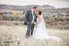 Bride and Groom in a romantic field against the Colorado mountains on their wedding day.  Venue Willow Creek Manor.  Katie Corinne Photography