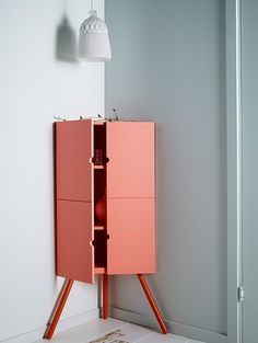 Pink wooden IKEA corner cabinet with a white glass lampshade hanging above it.