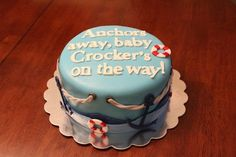 lifebelts in white and red, white rope and dark blue anchors, decorating a smooth light blue cake, nautical baby shower cakes, with a festive message, written in white fondant