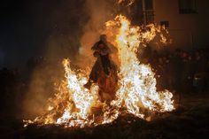 """A man rides a horse with a child through the flames during the """"Luminarias"""" annual religious celebration on 1/16/14, the eve of Saint Anthony's day, which celebrates the patron saint of animals. The photo was taken in the village of San Bartolome de los Pinares, Spain. According to a tradition that dates back 500 years, people ride their horses through the narrow cobblestone streets of this small village to purify the animals with the smoke of the bonfires."""
