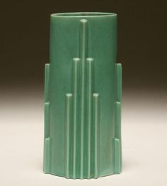 """Deco art pottery vase in matte green with stylized skyscraper design on body. 10""""H. Good condition with nick on base."""