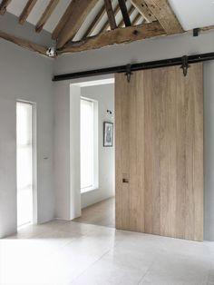 schuifdeur tussen woonkamer en keuken gemaakt van stijgerhout